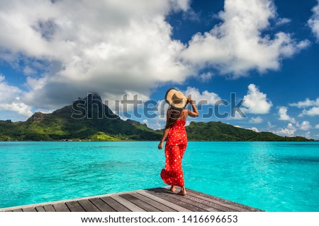 Bora Bora island luxury resort hotel woman relaxing at view of Mt Otemanu in Tahiti, French Polynesia Honeymoon travel destination for summer vacation. #1416696653