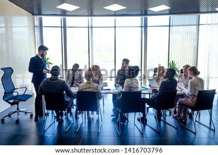 a group of successful afro americans, europeans ,arabic and korean businessman and businesswoman working in the office with large glass windows Royalty-Free Stock Photo #1416703796