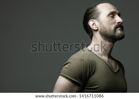 Fabulous at any age. Profile portrait of charismatic muscular 40-year-old man standing over dark gray background. Hair brushed back. Rocker, biker style. Close up. Copy-space. Studio shot #1416711086