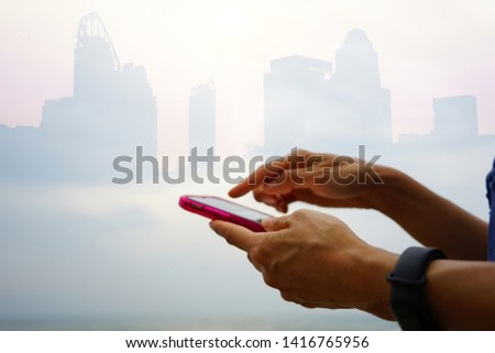Female hand holding and using smartphone on blurred background of gradient silhouette city building. Technology's impact on people's live concept. (selective focus, space for text) Royalty-Free Stock Photo #1416765956