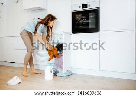 Young woman putting dirty clothes into the washing machine on the kitchen at home #1416839606