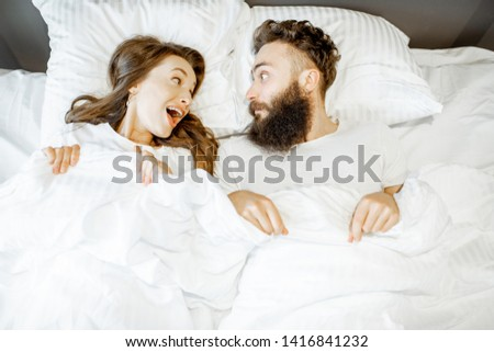 Portrait of a young couple feeling surprised and shocked lying together on the bed under the white sheets #1416841232