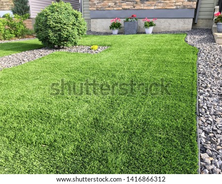 A beautiful artificial lawn in the front yard with nice flowers and shrubs surrounding it #1416866312