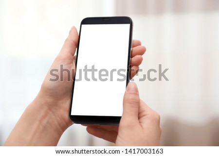 Woman holding smartphone with blank screen on blurred background, closeup of hands. Space for text #1417003163