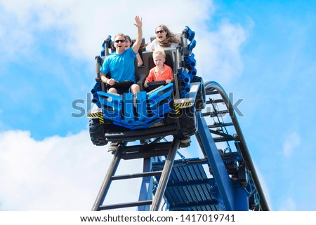 Young family having fun riding a rollercoaster at a theme park. Screaming, laughing and enjoying a fun summer vacation together. #1417019741