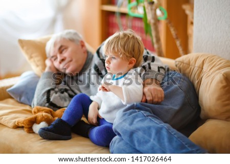 cute little toddler boy and grandfather watching together tv show. Baby grandson and happy retired senior man sitting together at home with cartoons on television. Calm family time #1417026464