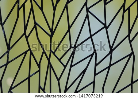 Abstract picture of a window made of polygonal pieces of glass. Artistic design with many black lines and a blur green grey background. Decorative element.