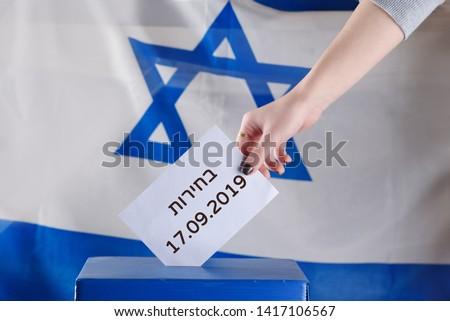 Israeli woman votes on election day. Close up of hand. Hebrew text Elections 17.09.2019 on Israel flag background. Israel to hold new elections 17 September 2019 after ruling coalition talks fail. #1417106567