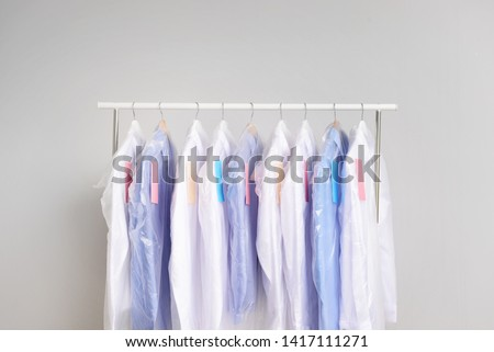 Rack with clothes after dry-cleaning on light background #1417111271