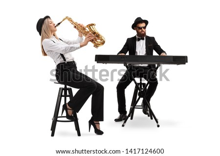 Full length shot of a female saxophonist and a male keyboard player isolated on white background