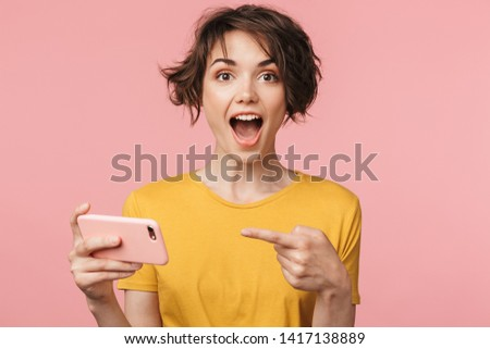 Image of a shocked young beautiful woman posing isolated over pink wall background play games by mobile phone. #1417138889