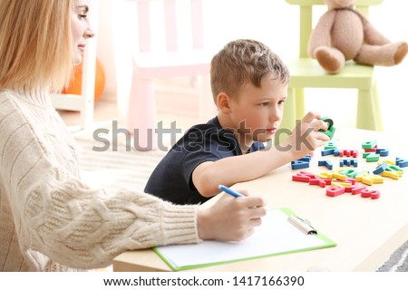 Female psychologist working with boy suffering from autistic disorder Royalty-Free Stock Photo #1417166390