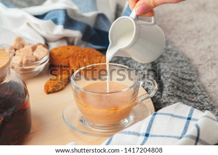 Hot masala chai, tea with milk poured over close up #1417204808
