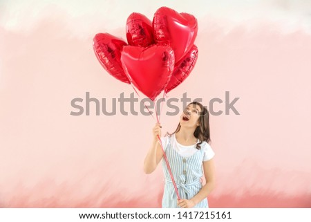 Beautiful young woman with heart shaped air balloons on color background #1417215161