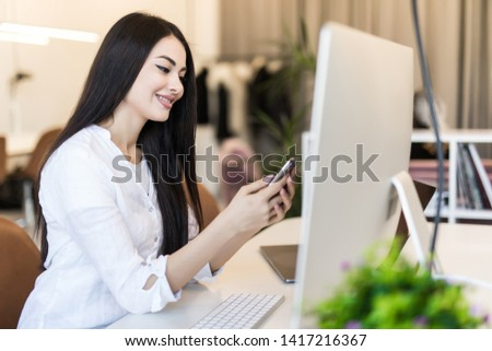 Portrait of beautiful young businesswoman working on laptop and use phone in office #1417216367