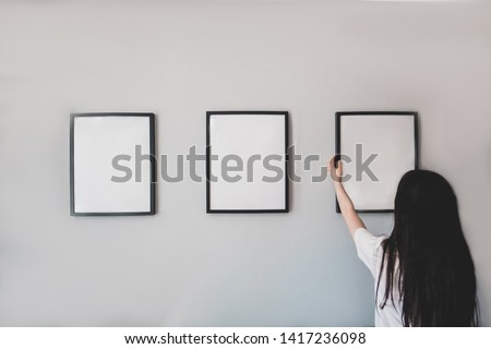 Girl hangs a frame on the wall. Empty place for your photo, picture, gratitude letter, design or logo. Horizontal mockup