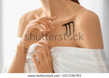 Woman with painted VIRGO Zodiac sign on her body indoors