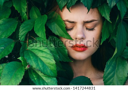 Female face close-up bright makeup closed eyes green leaves of bushes #1417244831
