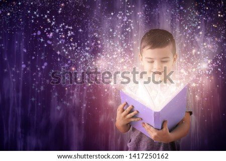 Cute little boy reading magic book on dark color background #1417250162