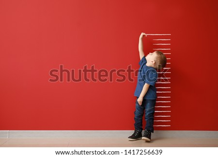 Little boy measuring height near color wall #1417256639