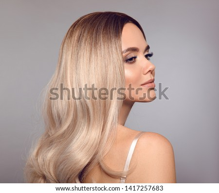 Ombre blond shiny hair. Beauty fashion blonde woman portrait. Beautiful girl model with makeup, long healthy hairstyle posing isolated on studio grey background. #1417257683