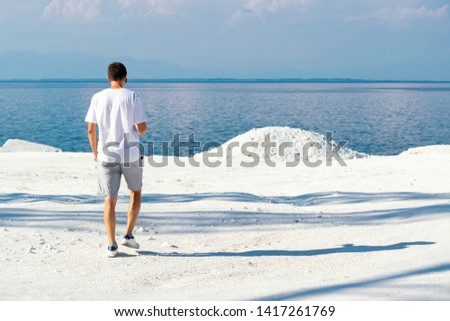 Young man walking at Marble beach the famous place on island Thassos in Nothern Greece. The only snow white marble in Europe. Unique place concept #1417261769