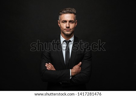 Handsome confident businessman wearing suit standing isolated over black background, arms folded Royalty-Free Stock Photo #1417281476