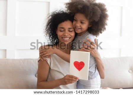 Happy young african american single mom embracing little cute child daughter thanking for gift, smiling black mum hugging small kid holding greeting card with red heart bonding on mothers day concept
