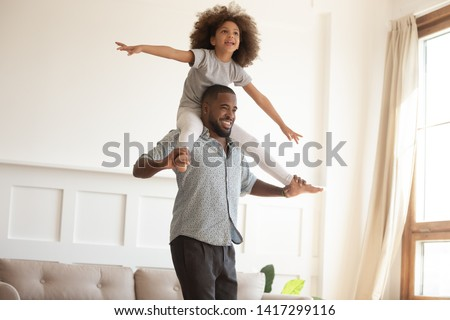 Loving black dad giving cute little kid daughter piggyback ride at home, happy african american father playing carrying funny small child girl on back flying bonding having fun laughing indoors #1417299116