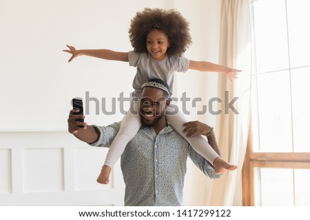 Happy african dad wearing crown piggybacking little funny daughter taking selfie at home, loving black father carrying cute small kid on back holding phone make photo playing together in living room #1417299122