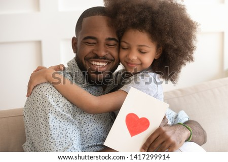 Happy affectionate african american dad embracing little child daughter holding greeting card with red heart bonding on fathers day concept, smiling cute kid girl hug daddy congratulate make surprise #1417299914