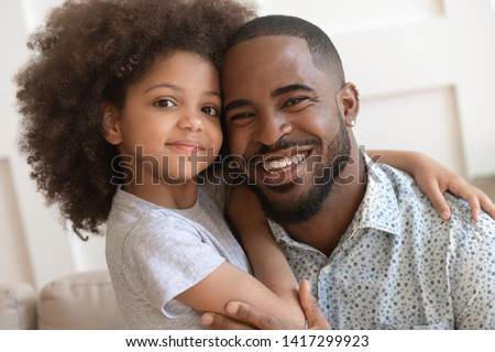 Happy affectionate african american family young daddy and small cute child daughter portrait, loving black dad and little mixed race kid girl bonding embrace looking at camera on fathers day concept #1417299923