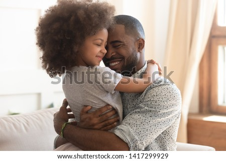 Sweet moments of fatherhood concept, happy african father hold embrace cute little child daughter, smiling black family mixed race daddy and small kid hugging cuddling enjoying time together at home Royalty-Free Stock Photo #1417299929