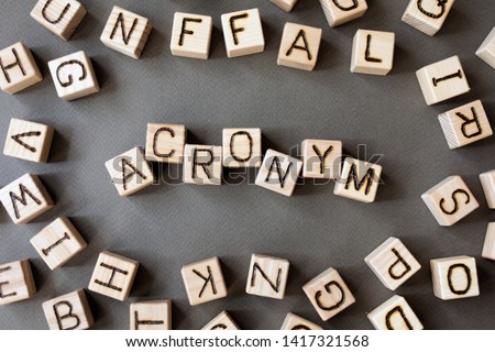 the word acronym wooden cubes with burnt letters, use of acronyms in the modern world, gray background top view, scattered cubes around random letters #1417321568