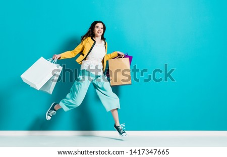 Cheerful happy woman enjoying shopping: she is carrying shopping bags and running to get the latest offers at the shopping center #1417347665