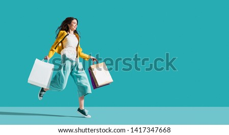 Cheerful happy woman enjoying shopping: she is carrying shopping bags and running to get the latest offers at the shopping center #1417347668