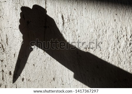 Shadow of the hand holding a big sharp knife. Murderer, killer or robber with a knife. Criminal. Crime. Horror scene. #1417367297