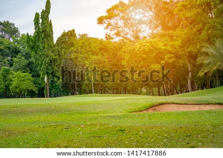 Golf course and beautiful fairway and layout on hills nature. white flag in hole on green golf, bunker near green and tree forest is background #1417417886
