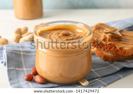 Glass jar with peanut butter, peanut, kitchen towel, spoon and peanut butter sandwich on white wooden background, space for text and closeup #1417429472