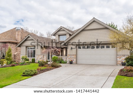Beautiful exterior of newly built luxury home. Yard with green grass and walkway lead to front entrance. #1417441442