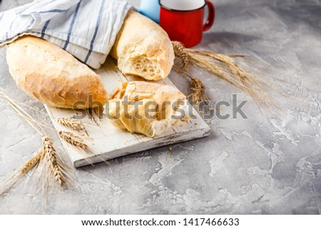 Wheat round bread in the form of a ring and spikelets on a wooden cutting board on a light concrete background. Big bagel. Space for text. #1417466633