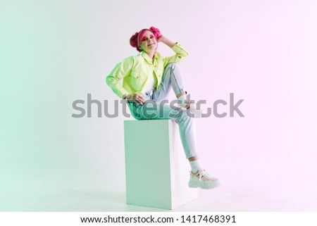 woman with pink hair sits on a cubed fashion