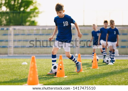 Football Drills: The Slalom Drill. Youth soccer practice drills. Young football players training on pitch. Soccer slalom cone drill. Boy in blue soccer jersey shirt running with ball between cones #1417475510