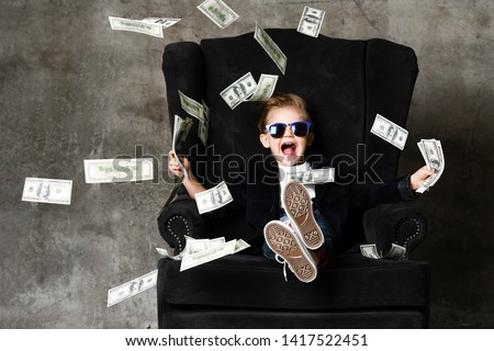 Happy shouting self-confident rich kid boy millionaire sitting with legs crossed in luxury armchair and throwing money dollars cash. Overspend. #1417522451
