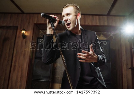 Portrait of handsome attractive singer singing hit with open mouth in microphone #1417599392