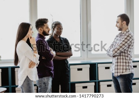 Informal meeting of team standing at break in modern office #1417790273
