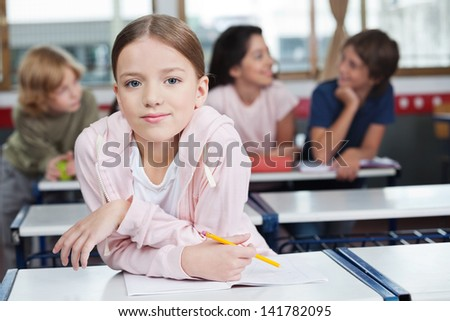 Portrait of little schoolgirl leaning on desk with students in background #141782095