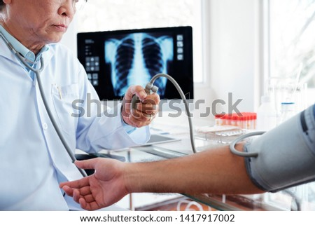 Serious general practitioner measuring blood pressure of young patient, chest x-ray on computer screen in background #1417917002