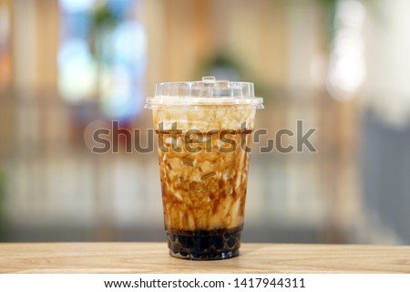 Bubble Milk Tea - A plastic glass of fresh milk with black sugar syrup (Kuromitsu) and hot black pearl (Boba) topped with cream cheese on blurred background, Taiwanese drinking culture.  #1417944311