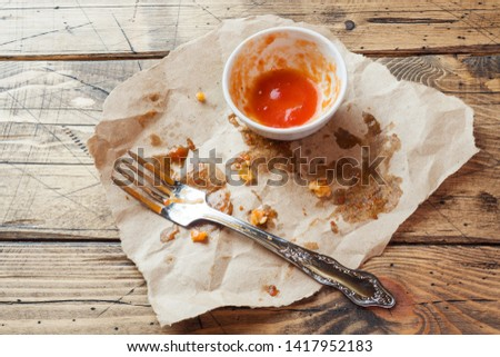 Dirty dishes after meals in oil and tomato sauce. Leftover food after eating chicken nuggets and sauce. Wooden background #1417952183